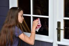 女孩清洁窗口 免版税库存照片