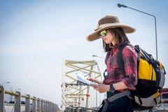 女孩游人在桥梁读了地图 免版税库存图片