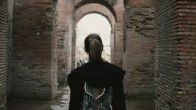 女孩游人在罗马,意大利的历史中心走 通过古老弧的链子妇女由红砖制成 股票录像