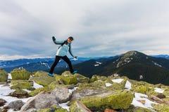 女孩游人表现出正面情感在一座多雪的山顶部 免版税库存照片