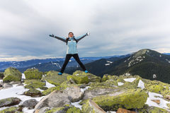 女孩游人表现出正面情感在一座多雪的山顶部 库存照片