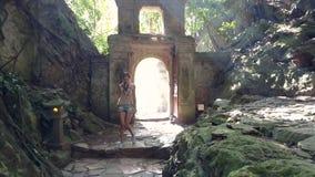 女孩游人通过石曲拱进入洞反对光 股票录像