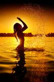 女孩游泳和飞溅在夏天海滩 免版税库存图片