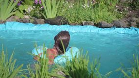 女孩游泳在一个小池塘 孩子在一个热的夏日享用凉水 愉快的童年 花和草增长 股票录像