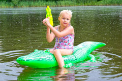 女孩游泳在有可膨胀的鳄鱼的河 免版税图库摄影