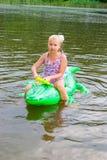 女孩游泳在有可膨胀的鳄鱼的河 免版税库存图片