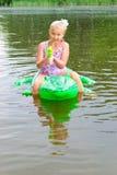 女孩游泳在有可膨胀的鳄鱼的河 库存照片