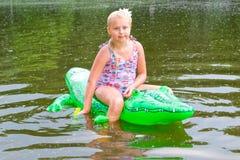 女孩游泳在有可膨胀的鳄鱼的河 库存图片