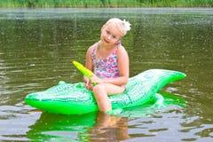 女孩游泳在有可膨胀的鳄鱼的河 免版税库存照片