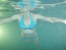 女孩游泳在水池的水下 免版税库存图片