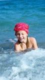 女孩游泳在海和使用在沿海小条 免版税库存照片