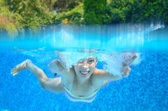 女孩游泳在游泳池,水中和在看法上 库存照片