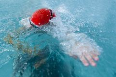 女孩游泳在蓝色游泳池的水表面下 免版税库存照片