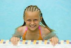 女孩游泳池边微笑年轻人 免版税库存图片