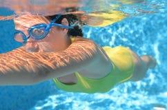 女孩游泳者在水池的游泳自由式,在水视图、体育和健身下 库存照片