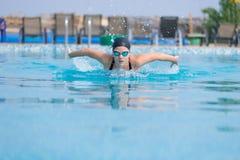 女孩游泳蝶泳样式 免版税图库摄影
