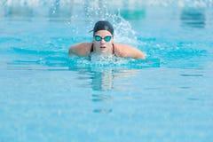女孩游泳蝶泳样式 免版税库存图片