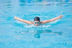 女孩游泳蝶泳样式 免版税库存照片