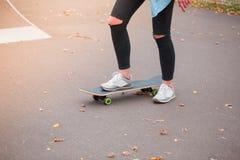 女孩溜冰者站立与在一个滑板的一只脚在冰鞋公园 免版税库存照片