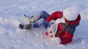 女孩滚动下来在雪橇的小山在雪 女孩戏剧在冬天在公园 慢的行动 股票视频