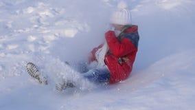 女孩滚动下来在雪橇的小山 雪飞行到面孔的,愉快的女孩戏剧孩子在公园在冬天 慢的行动 股票视频