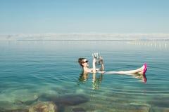 女孩漂浮在表面死海的读书报纸享受夏天太阳和假期 休闲旅游业,健康生活方式,自由的蒂姆 图库摄影