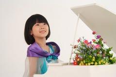 女孩演奏玩具的少许钢琴 库存图片