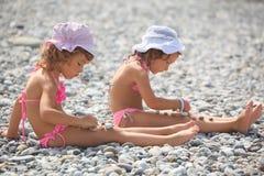 女孩演奏石头的少许小卵石 免版税库存图片