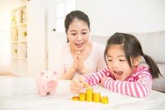 女孩激动看她的储蓄金钱 免版税库存图片
