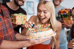 女孩点燃在蛋糕的蜡烛 在她附近有等待庆祝的客人 免版税图库摄影