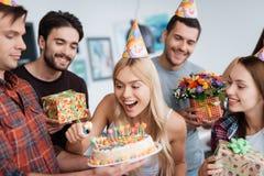 女孩点燃在蛋糕的蜡烛 在她附近有等待庆祝的客人 免版税库存图片