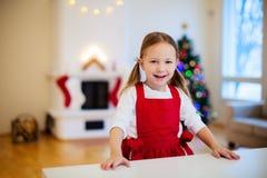女孩烘烤圣诞节曲奇饼 免版税库存照片