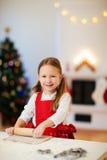 女孩烘烤圣诞节曲奇饼 免版税库存图片