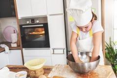 女孩烘烤在家庭厨房里 库存图片