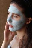 女孩照料她的脸色分层堆积的润肤霜 免版税库存照片