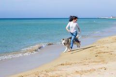 女孩狗奔跑 库存图片