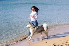 女孩狗连续海滩 免版税库存照片