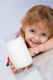 女孩玻璃愉快的小的牛奶 库存照片