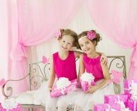 女孩生日,有当前礼物盒的孩子减速火箭的桃红色礼服 库存照片
