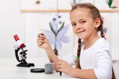 女孩生物课的研究植物 免版税库存照片