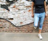 女孩生活方式画象反对五颜六色的都市砖墙背景的 免版税库存图片