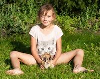 女孩用兔子坐草甸 免版税库存图片