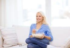 女孩用准备好的玉米花观看电影 免版税图库摄影