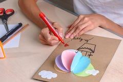 女孩用剪刀,色纸切开,坐在桌上 免版税库存照片