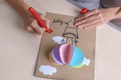 女孩用剪刀,色纸切开,坐在桌上 免版税库存图片