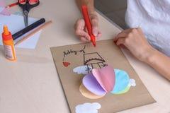 女孩用剪刀,色纸切开,坐在桌上 免版税图库摄影