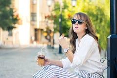 女孩用去的咖啡在街道上 免版税库存图片
