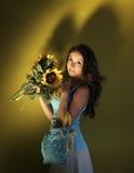 女孩用向日葵和袋子 免版税库存图片
