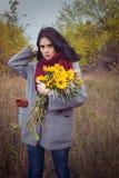 女孩用向日葵在秋天森林里站立 库存照片