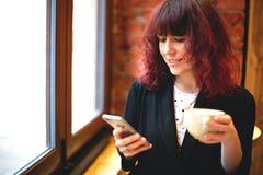 女孩用咖啡和电话 免版税库存照片
